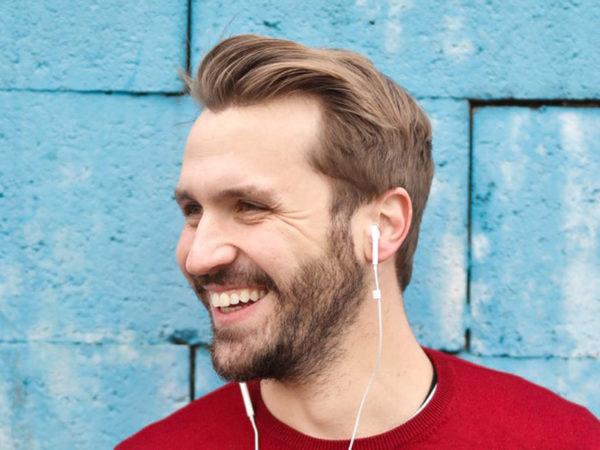 mann smiler med propper i øra