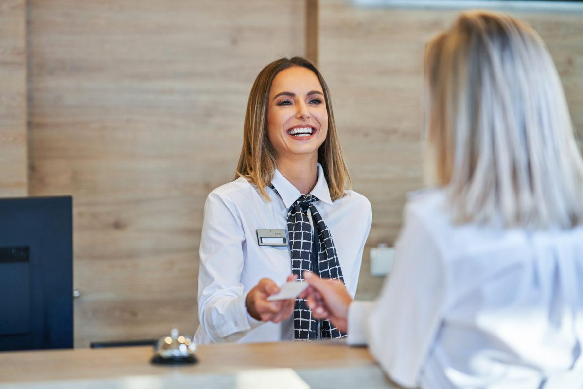 kvinne smiler og gir bort et kort ved en respsjon